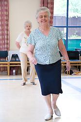 Older women taking part in a line dancing activity,