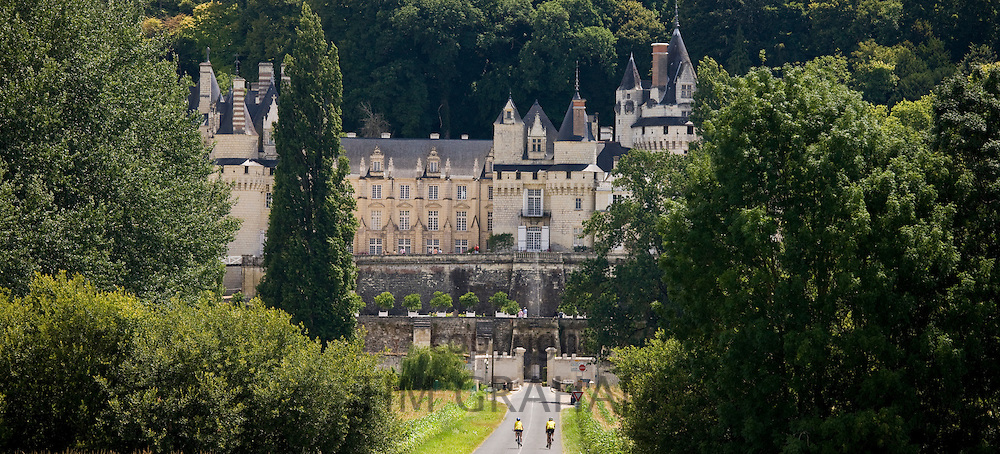 Cyclists at Chateau d'Usse at Rigny Usse from across the Indre River in the Loire Valley, France
