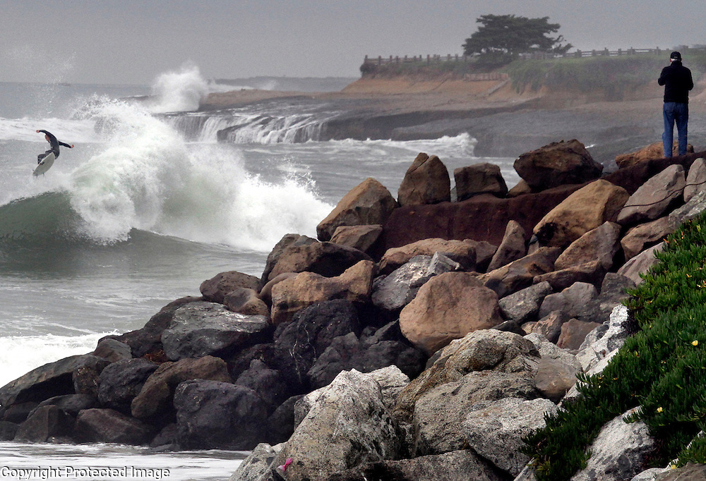 Mark Millenacker stands atop the bluff at the end of 20th Avenue in Santa Cruz, California to capture video of the storm-fueled waves beginning to roll into the Central California coastline as a surfer grabs some air at the end of a ride.<br /> Photo by Shmuel Thaler <br /> shmuel_thaler@yahoo.com www.shmuelthaler.com