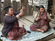 Two Brokpa women spinning yak hair using drop spindles called Yoekpa, Merak, Eastern Bhutan. The Brokpa, the semi-nomads of the villages of Merak and Sakteng are said to have migrated to Bhutan a few centuries ago from the Tshona region of Southern Tibet. Thriving on rearing yaks and sheep, the Brokpas have maintained many of their unique traditions and customs. Their distinctive hat known as 'tsipee cham' is made of yak felt with long twisted tufts, said to keep the rain from running onto their faces.