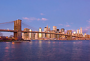 Skyline view of Lower Downtown Manhattan seen from the East River showing the Brooklyn Bridge and the skyscrapers of the Financial District, New York City.