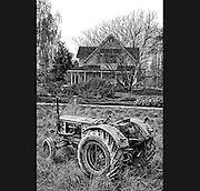 Deutz tractor by in field by farmhouse.