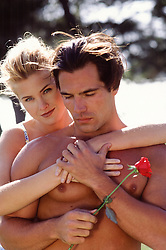 sexy romantic couple outdoors holding a rose