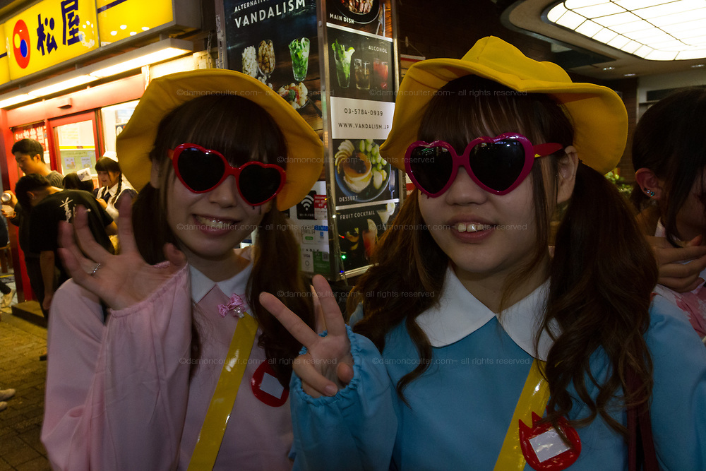 Two Japanese girls dressed as elementary school students with heart sunglasses during the Halloween celebrations Shibuya, Tokyo, Japan. Saturday October 27th 2018. The celebrations marking this event have grown in popularity in Japan recently. Enjoyed mostly by young adults who like to dress up, drink , dance and misbehave in parts of Tokyo like Shibuya and Roppongi. There has been a push back from Japanese society and the police to try to limit the bad behaviour.