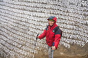 Trekker Liana Welty poses besides a huge mani stone carved and painted with Tibetan Buddhist prayers (mantras) above Namche Bazaar on the trail to Everest Base Camp, Khumbu region, Sagarmatha National Park, Himalaya Mountains, Nepal.