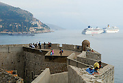 Section of city wall, Dubrovnik old town, Croatia, with cruise ships and replica sailing ship in background