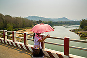15 MARCH 2013 - ALONG HIGHWAY 13, LAOS:  School girls cross the Nam Oh Bridge on Highway 13 in Luang Prabang province. The paving of Highway 13 from Vientiane to near the Chinese border has changed the way of life in rural Laos. Villagers near Luang Prabang used to have to take unreliable boats that took three hours round trip to get from the homes to the tourist center of Luang Prabang, now they take a 40 minute round trip bus ride. North of Luang Prabang, paving the highway has been an opportunity for China to use Laos as a transshipping point. Chinese merchandise now goes through Laos to Thailand where it's put on Thai trains and taken to the deep water port east of Bangkok. The Chinese have also expanded their economic empire into Laos. Chinese hotels and businesses are common in northern Laos and in some cities, like Oudomxay, are now up to 40% percent. As the roads are paved, more people move away from their traditional homes in the mountains of Laos and crowd the side of the road living off tourists' and truck drivers.   PHOTO BY JACK KURTZ