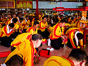 """02 JUNE 2017 - SAMUT SAKHON, THAILAND: Men pray before the City Pillar Shrine parade in Samut Sakhon. The Chaopho Lak Mueang Procession (City Pillar Shrine Procession) is a religious festival that takes place in June in front of city hall in Samut Sakhon. The """"Chaopho Lak Mueang"""" is  placed on a fishing boat and taken across the Tha Chin River from Talat Maha Chai to Tha Chalom in the area of Wat Suwannaram and then paraded through the community before returning to the temple in Samut Sakhon. Samut Sakhon is always known by its historic name of Mahachai.      PHOTO BY JACK KURTZ"""