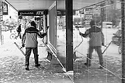 Snow shoveler and reflection in a downtown Missoula building. Missoula Photographer, Picture of Missoula