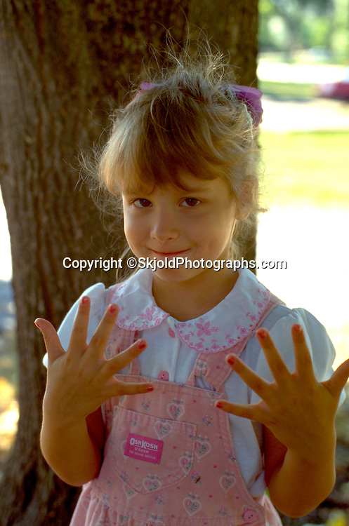 5 Year old girl drying painted nails.   WesternSprings  Illinois USA
