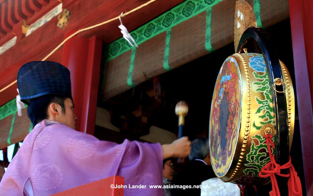 Shinto priest, banging drums during a wedding ceremony at Tsurugaoka Hachimangu Shrine in Kamakura.