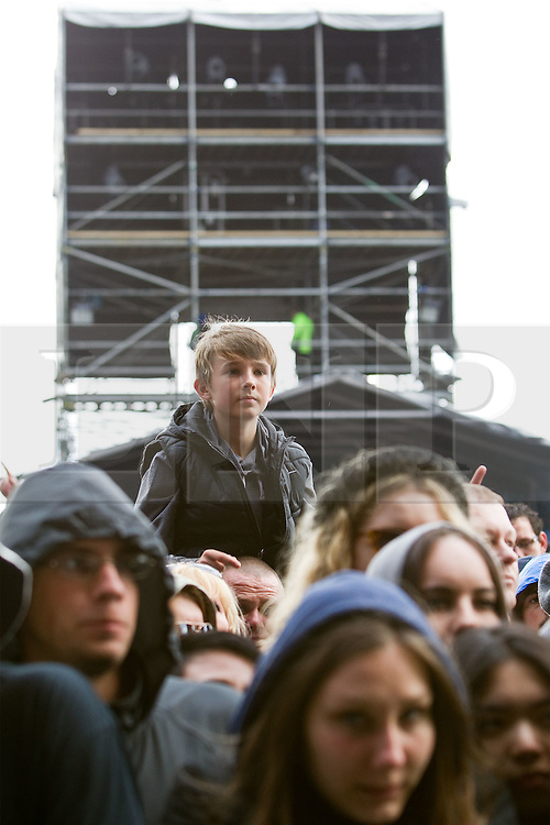 © licensed to London News Pictures . 30/06/2012 . Manchester , UK . The Wailers perform on stage at Heaton Park as warm up for the Stone Roses , who are on their comeback tour . A boy sits on a man's shoulders to get a view of the stage from the crowd . Photo credit : Joel Goodman/LNP