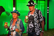 """Shangri La is a festival of contemporary performing arts held each year within Glastonbury Festival. The theme for the 2015 Shangri La was Protest. A couple, man and woman in their 50s, dressed in festival gear, holding drinks, in front of the """"House of Come-Ons"""" club"""