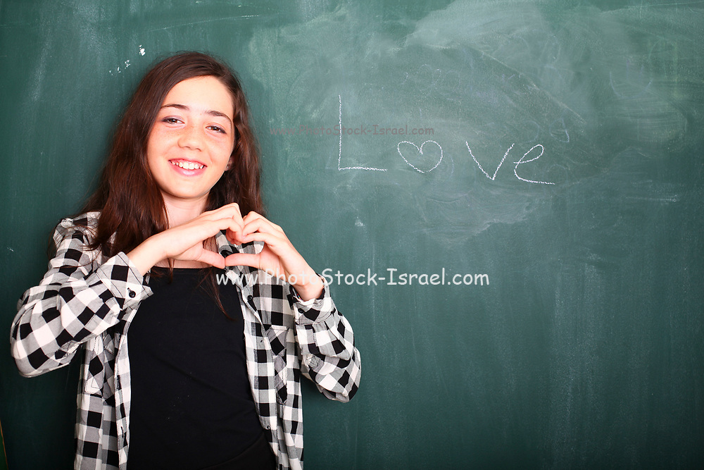 Young pre-teen girl of 12 waiting for love at a blackboard