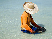 Marie Clar Labtik (50) sits in the sea collecting small shells for making necklaces and other products for tourists, Pooc, Bantayan Island, The Philippines.