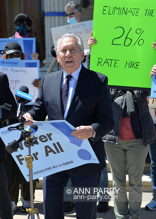 Mineola, New York, USA. April 26, 2021. At front, GEORGE POMBAR, President of the Glen Head-Glenwood Civic Association, speaks at rally. Faced with a 26% rate increase from New York American Water going into effect May 1, 2021, activists and residents who are NYAW customers rally to urge NYS Assemby to push through legislation, before that date, corresponding with NYS Senate Bill S989A to establish a Nassau County Water Authority and except water works corporations in counties of populations over one million from a special franchise tax. Rally was held in front of Theodore Roosevelt Executive and Legislative Building.