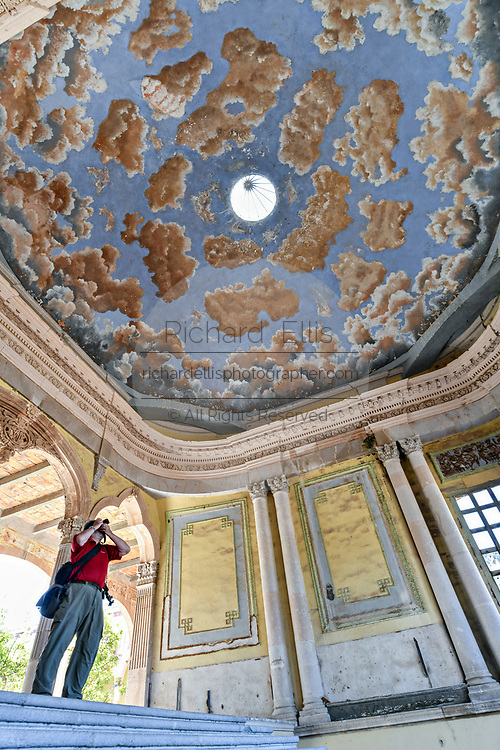A photographer takes a photo of the painted ceiling on the grand stairs of the derelict and fading Hacienda de Jaral de Berrio in Jaral de Berrios, Guanajuato, Mexico. The abandoned Jaral de Berrio hacienda was once the largest in Mexico and housed over 6,000 people on the property and is credited with creating Mescal.