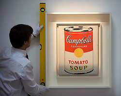 © licensed to London News Pictures. London, UK  17/06/2011. A Sotheby's worker hangs 'Campbells Soup Can (Tomato)' by Andy Warhol, which is estimated to fetch up to £4.5 million at auction as part of Sotheby's upcoming auction of Contemporary art. Please see special instructions for usage rates. Photo credit should read Ben Cawthra/LNP