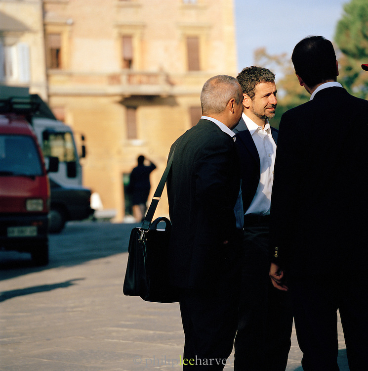 Businessmen in conversation at the Piazza Del Campo, Siena, Tuscany, Italy