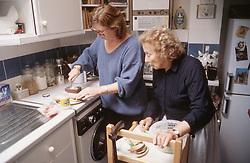 Elderly woman with daughter preparing food in kitchen,