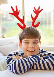 Smiling Boy Wearing Christmas Antlers