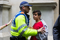 London, June 24th 2017. Anti-fascist protesters counter demonstrate against a march to Parliament by the far right anti-Islamist English Defence League. PICTURED: A police officer pushes a young EDL supporter away from a group of anti-fascists near Trafalgar Square.