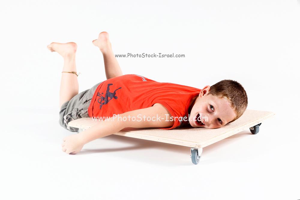 Indoor playground boy plays on wheeled board On white Background