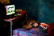 Aadite, 9, a disabled boy affected by microcephaly, cerebral palsy and malnutrition, is watching cartoons while laying motionless on a bed inside his home in Kabit Pura, near the abandoned Union Carbide (now DOW Chemical) industrial complex in Bhopal, central India. Aadite's father, Raju, a '1984 Gas Survivor', died in March 2013 at the age of 32, due to lungs failure. Because of his mother's need to act as the family's breadwinner, Aadite cannot attend the programs run by 'Chingari Trust Rehabilitation Centre', one of two vital medical institutions funded by 'The Bhopal Medical Appeal'. Lakshmi, 29, works six days a week as a cleaner, and Aadite is looked after by his two sisters Mayuri, 13, Mahag, 8, and his younger brother Anuj, 6. None of the siblings in this family are attending school or any kind of practical education.