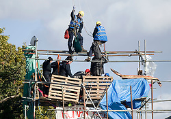 © Licensed to London News Pictures. 19/10/2011. Crays Hill, UK. Bailiffs use a crane to access a structure made by activists at the entrance to Dale Farm travellers site. Residents at Dale Farm, the UK's largest illegal traveller site being evicted today (19/10/2011) following a long dispute with Basildon Council . Travellers and activist had barricaded themselves in to the site in an attempt to prevent their eviction. Photo credit: Ben Cawthra/LNP