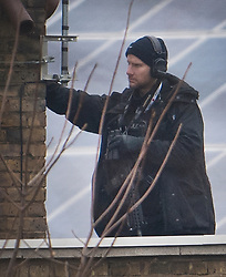 © Licensed to London News Pictures. 18/12/2016. London, UK. An armed policeman stands on a nearby roof as a siege continues in Brixton. Police arrived after receiving reports of 'a man with a gun' at a house in a residential road near Brixton Prison. Photo credit: Ben Cawthra/LNP
