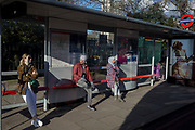 Passengers await the next service at a bus stop at Hyde Park Corner, on 7th March 2018, in London England.