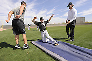 GLENDALE, AZ - FEBRUARY 25:  Omar Vizquel #11 of the Chicago White Sox practices sliding as strength coaches Allen Thomas (L) and Dale Torborg look on during a spring training workout on February 25, 2011 at Camelback Ranch in Glendale, Arizona. (Photo by Ron Vesely)