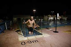 © Licensed to London News Pictures. 29/03/2021. London, UK. Swimmers excercise at Hampton Pool in south west London before dawn. The pool opened for the return to outdoor swimming at 4:44am. Covid regulations have changed today to allow gatherings up to six people outdoors. With sporting facilities, such as tennis,basketball courts and outdoor swimming pools allowed to reopen. Photo credit: Peter Macdiarmid/LNP