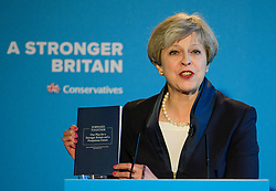 © Licensed to London News Pictures. 18/05/2017. Halifax, UK.  British Prime Minister THERESA MAY holds a copy of the manifesto, while speaking at the launch event for the Conservative Party manifesto at The Arches in Halifax, West Yorkshire. The Conservatives are the last of the three main parties to launch their manifesto ahead of a snap general election called for June 8, 2017. Photo credit: Ben Cawthra/LNP