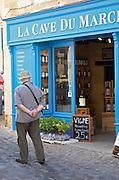 Wine shop. La Cave du March with an senior man looking. The town. Saint Emilion, Bordeaux, France
