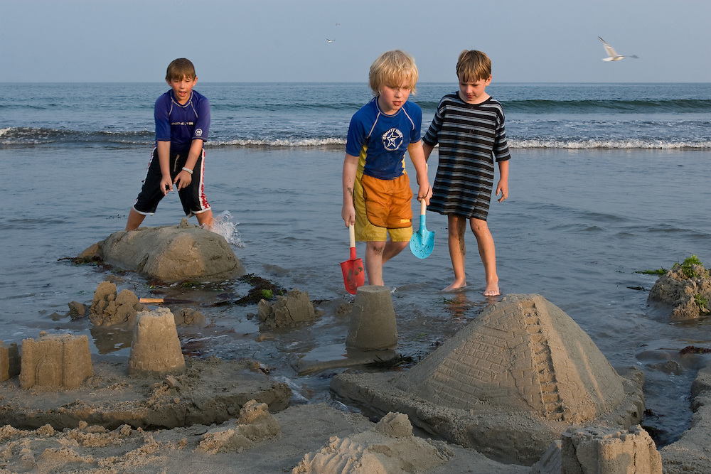 Boys build sandcastles on the beach in Narragansett, Rhoe Island, as the tide comes in behind them.