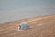 Family sitting on beach under large black and white umbrella, Felixstowe, Suffolk, England