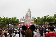 A woman wearing Minnie Mouse ears walks through Walt Disney Co.s Shanghai Disneyland theme park  towards the iconic castle during a trial run ahead of its official opening, in Shanghai, China, on Wednesday, June 8, 2016. The $5.5 billion Shanghai Disneyland is one  of the most profitable Disney ventures in the world and the first theme park on mainland China.