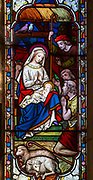 Stained glass window of nativity scene with baby Jesus in crib with shepherds watching, circa 1870 by Ward and Hughes, church of Saint Andrew, Bramfield, Suffolk, England, UK