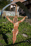 A sheet metal Jesus crucifix a popular local copy from an historical Rutherian church outside an abandoned industrial building on the outskirts of Jaworki, on 20th September 2019, <br /> near Szczawnica, Malopolska, Poland. The village of a thriving Rutherian community was once in nearby Biala Woda where over 100 farms were located - the remains of which are still seen. A wooden cross with a figure of Christ cut from sheet metal survived the culture. Similar crosses and chapels can be found in the colloquial language of White Water  in the Romanian, Ukrainian or Eastern Slovakia Carpathians.
