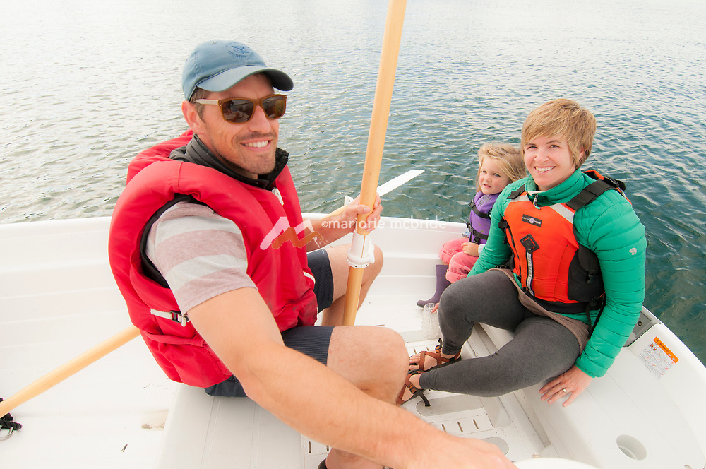 Family smiling while on a boat ride from Lummi Island, San Juan Islands, Puget Sound. WA