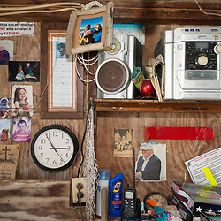 "August 4, 2017 - Tangier Island, VA - Inside Mayor James ""Ooker"" Eskridge's crab shack where pictures of his family share space with Confederate General Robert E. Lee, U.S. President Donald J. Trump, and a sticker that professes ""Earth is not my mother but He who created it is my Father."" Photo by Susana Raab/Institute"