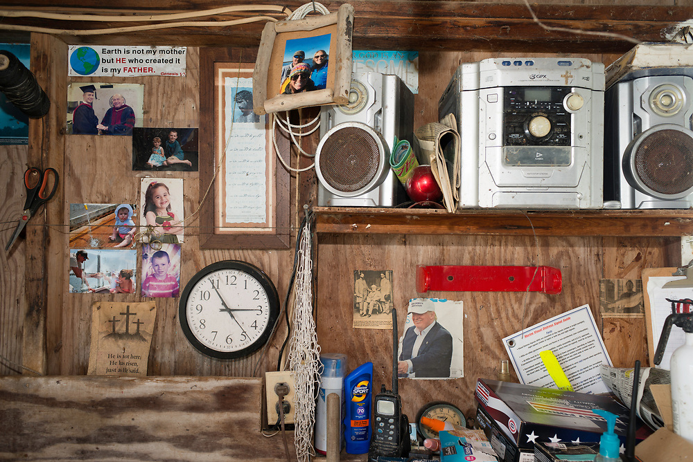 """August 4, 2017 - Tangier Island, VA - Inside Mayor James """"Ooker"""" Eskridge's crab shack where pictures of his family share space with Confederate General Robert E. Lee, U.S. President Donald J. Trump, and a sticker that professes """"Earth is not my mother but He who created it is my Father."""" Photo by Susana Raab/Institute"""