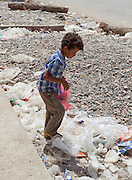 Boy sifting through rubbish on the street, Hadibu, Socotra, Yemen