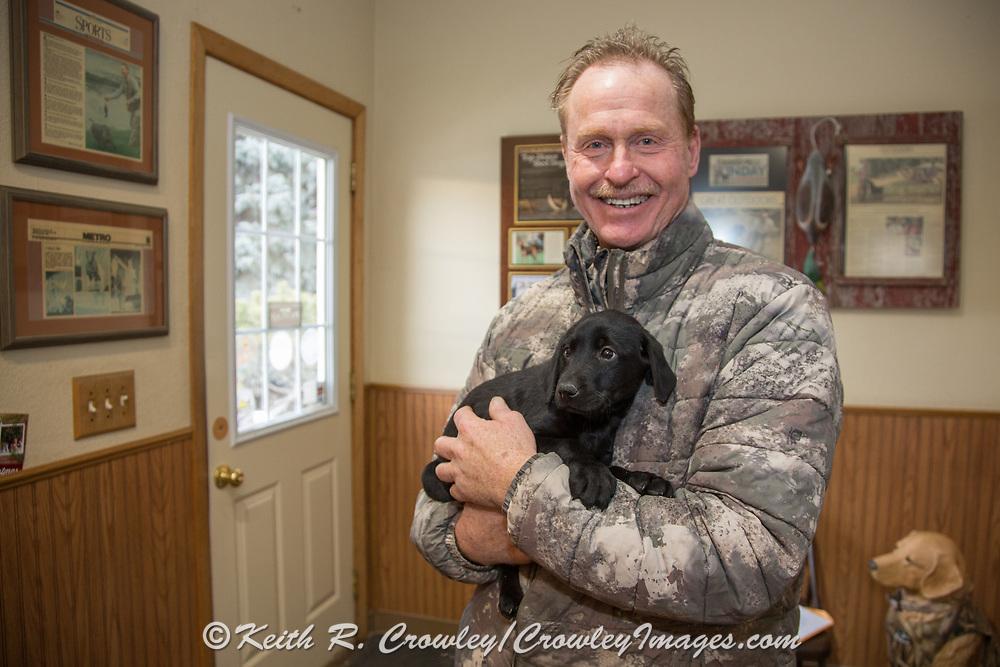 Tom Dokken holds a seven week old Black Lab pup at his Oak Ridge Kennels office in Minneosta