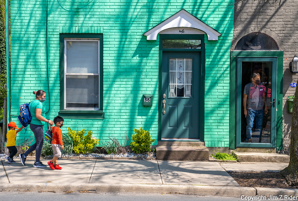With COVID masks secured, a mother walks her children home from school as a neighbor looks on in Lambertville, NJ, a regional tourist destination along the Delaware River with a wide variety of shops, galleries, bars, and restaurants.