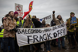 """© Licensed to London News Pictures . 26/01/2014 . Salford , UK . A banner that reads """" Balcombe and beyond frack off """" . Approximately 500 protesters march to an iGas fracking exploration site at Barton Moss , Salford , today (Sunday 26th January 2014) . They walk along the A57 road , blocking traffic as they do . A long term protest camp has been established on an access road leading to the site and today (26th January) protesters from other areas of the country travelled to the site to join with other protesters against fracking . Photo credit : Joel Goodman/LNP"""