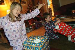 Children opening Christmas presents on Christmas Day morning; UK
