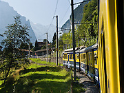 """Berner Oberland Bahn (BOB) enters Lauterbrunnen Valley  on narrow-gauge railway tracks in the Bernese Oberland region of Switzerland, the Alps, Europe. BOB serves Interlaken, Lauterbrunnen, and Grindelwald via a """"Y"""" junction at Zweilütschinen. At Wilderswil, BOB extends 7 km on Schynige Platte Railway. The trains are assisted in steep sections by rack and pinion (cog wheel drive). UNESCO lists """"Swiss Alps Jungfrau-Aletsch"""" as a World Heritage Area (2001, 2007)."""