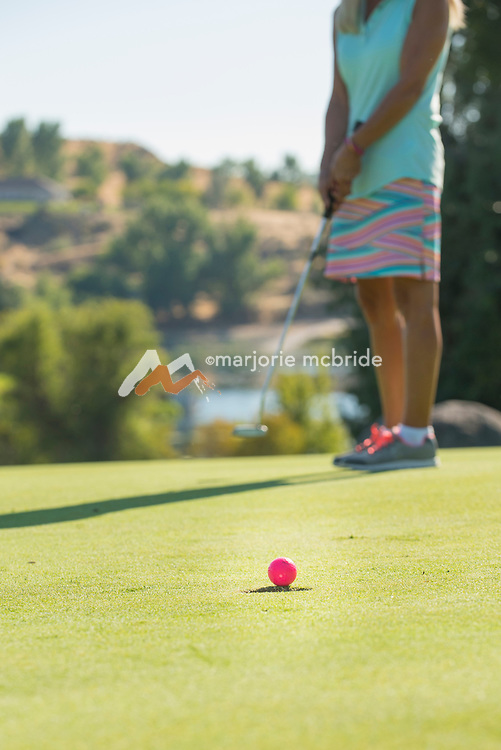 Senior woman putting on the 18th green in the canyon at the public course, Clear Lakes Country Club in Buhl, Idaho. MR